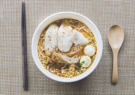 fish ball noodle with chopstick and wooden spoon