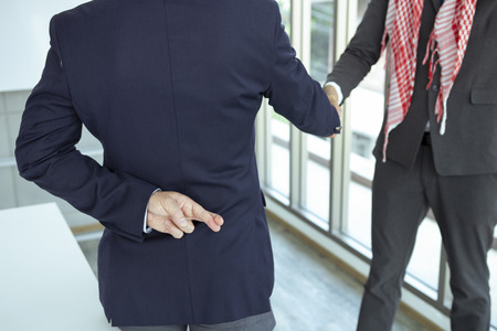 Arabian business  shaking hand with lie sign Stock Photo