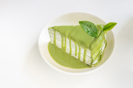 Green tea cage with greentea leaf on white plate