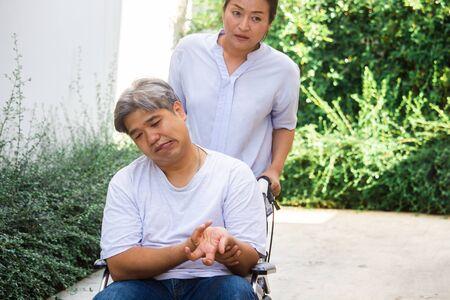Ein älteres Asien; Patient mittleren Alters sitzt im Rollstuhl, seine Frau kümmert sich um ihn. Gesundheit und medizinisches Konzept.