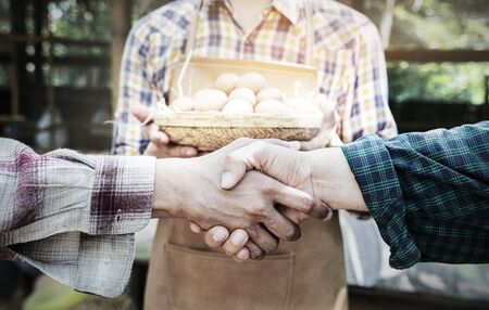 People shaking hands in a egg chicken farm,Handshake of business partners,farmers agreement. Agriculture agronomist food business contract concept