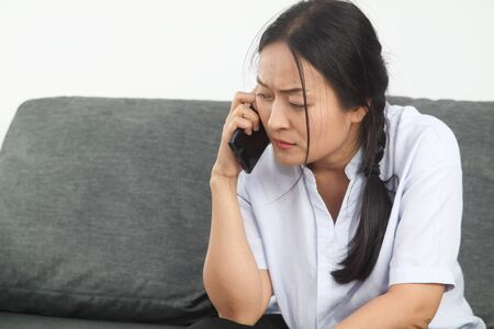 Middle-aged Asian woman is talking on the phone with seriousness. Stok Fotoğraf