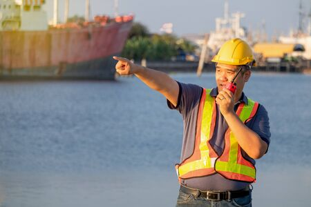 Workers are using radio communication and pointing forward at the shipping port. Stok Fotoğraf