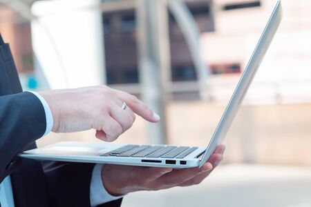 Close up hand of Young business man uses a laptop to find information about investments and businesses