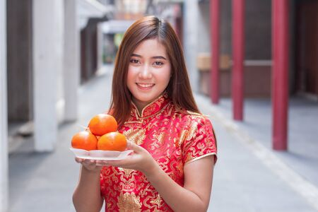 The girl wears a cheongsam costume, holding oranges. Oranges are auspicious fruit used for blessings during the Chinese New Year.
