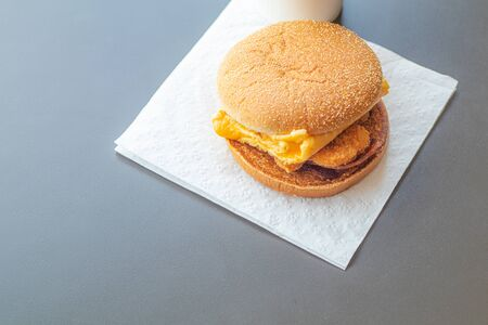 The hamburger was placed on toilet paper. On a gray table in a fast food shop table top view. Reklamní fotografie