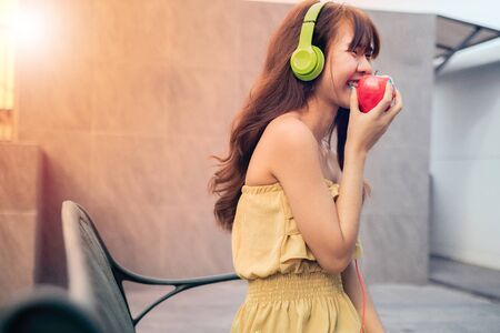 Euphoric woman listening music with headphone and eating red apple beside swimmimngpool, happy and smile concept.