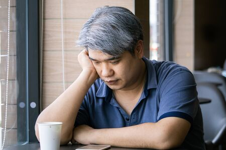 Stressed tired young Asian middle-aged man,old man take hand on head feeling depression and exhausted sitting by the window at coffee shop,grey hair man ,Family issues.