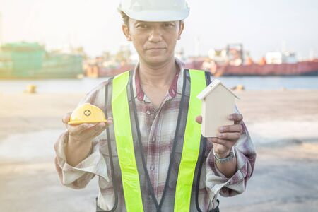 An engineer with a helmet and a small wooden house symbol for engineering and safety Reklamní fotografie