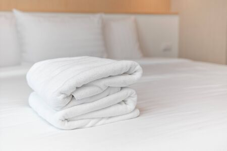 Close-up: The white towels are neatly folded and placed on the white bed. Hotel services Stock Photo