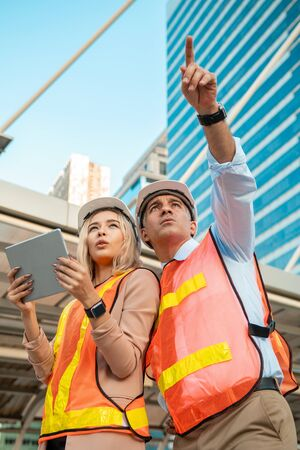 Both male and female engineers wear helmets. Standing in the construction zone while the female engineer was holding the tablet against building ,city view.