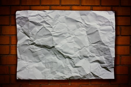 Blank White Crumpled paper on brick wall