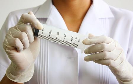 surgical needle: young nurse holding syringe isolated on white background.