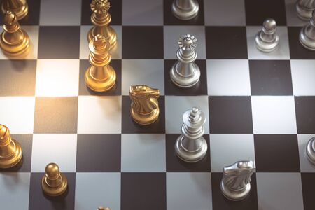 Chess game, set the board waiting to play in both gold and silver pieces detail blur