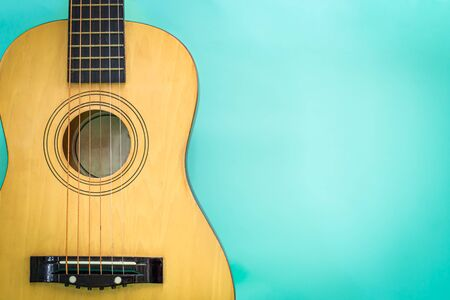 Acoustic guitar resting against a green background detail object Stock Photo
