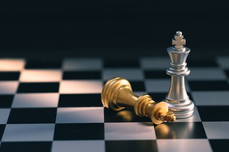 silver chess king standing and golden chess king falling on chess board detail art Stock Photo