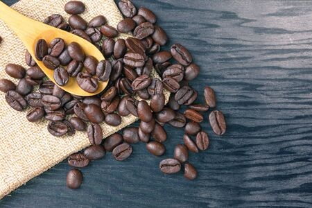 Coffee beans are scattered in wooden spoons and on sack bags and wooden patterned background detail art