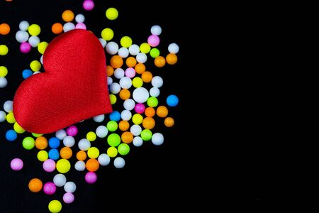 Red heart with multicolored foam beads on a dark black background detail art Stockfoto