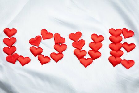 Many red hearts print the word love on a wrinkled white background detail object art Stockfoto