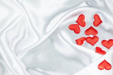 Many red hearts on a wrinkled white background detail object