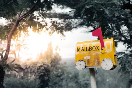 Closeup yellow old mailbox on a natural background detail blur Stockfoto