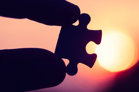 Silhouette of closeup hand holding the jigsaw puzzle against the evening sun detail symbol art