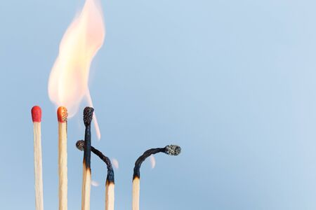 Matches in group burning safety-match with red, orange, yellow fire. Isolated on blue sky background detail object art