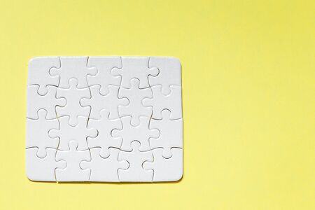jigsaw White puzzle on yellow background top view detail object art Stockfoto