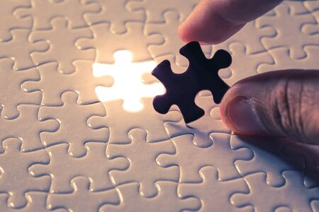 Hand holding piece of blank jigsaw puzzle detail blur