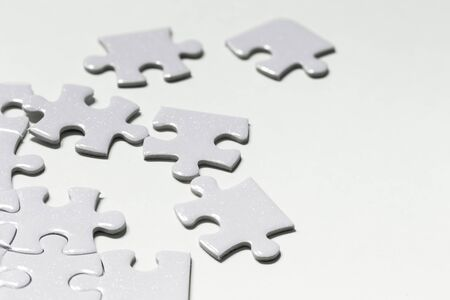 Closeup jigsaw puzzle white piece on white backdrop Stockfoto