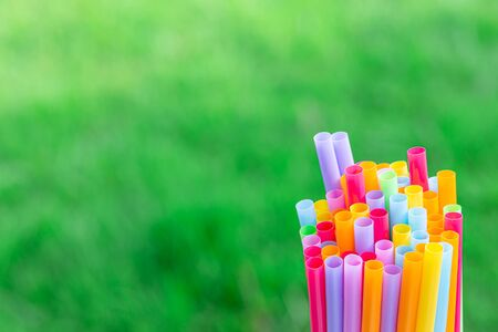 Multiple color drinking straws on a green grass background detail blur art