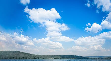 Blue sky and white clouds on the mountain and lake water detail nature background