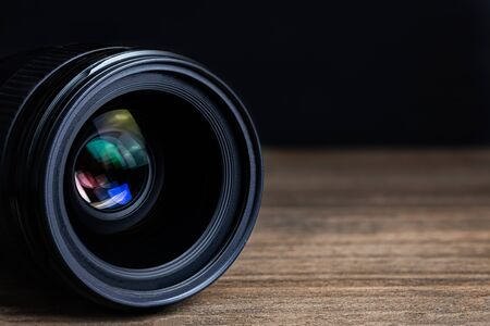 Closeup camera lens on a wooden floor with black dark background blur detail object isolated Archivio Fotografico
