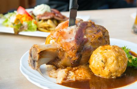 Traditional Bavarian roast pork knuckle with dumplings.