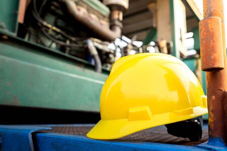 Gele veiligheidshelm of veiligheidshelm wordt op het werkplatform van de pompeenheid in olieveldbedrijf geplaatst. Geselecteerde focus op de bouwvakker. Veiligheid, geen ongeval op de foto van het werkplekconcept. Stockfoto