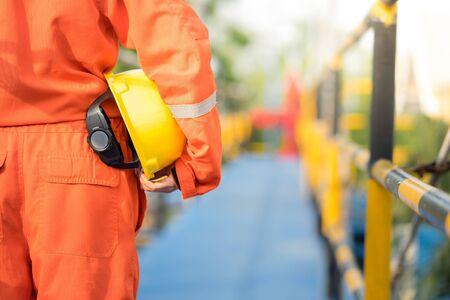 Travailleur de gisement de pétrole, technicien, opérateur avec casque de sécurité sur la plate-forme à pied avant l'heure du coucher du soleil. Banque d'images