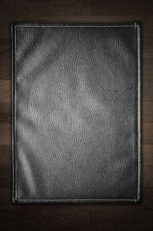 cowhide: A black leather texture isolated on the wooden background.