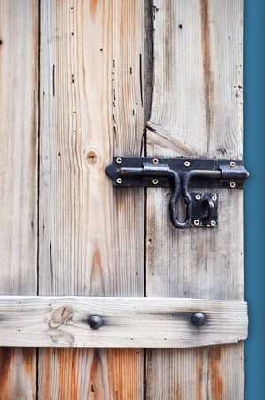 A bolt is on the wooden door and isolated on the blue background. photo