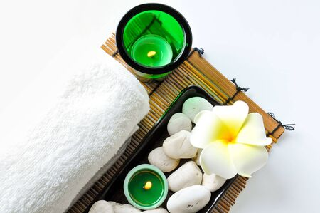 Two candle in a glass bowl ,A white towel , a plumeria and stones are on black tray .All isolated on white background.