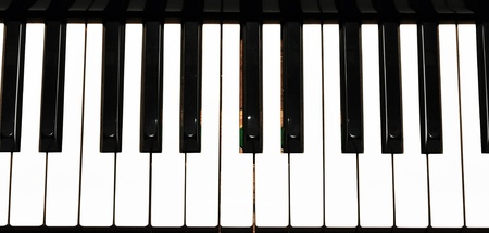 acoustically: Top view  piano keyboard. Antique piano with strong,dramatic lighting.