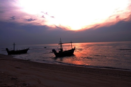Two longtail boats on the beach in sunset. photo
