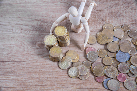 health care funding: A wooden doll man with his savings, gold coin. All composed with thai baht twenty-five and fifty cent Stock Photo