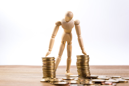 return on investment: A wooden doll man with his savings, gold coin. All composed with thai baht twenty-five and fifty cent Stock Photo