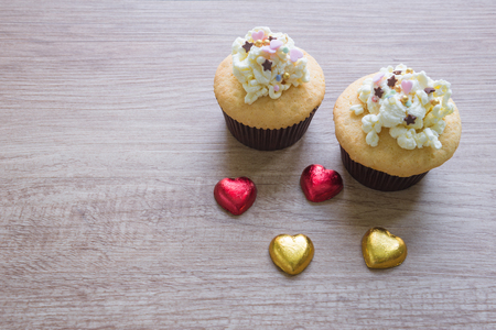 Cupcakes with heart shaped chocolate on wooden floor