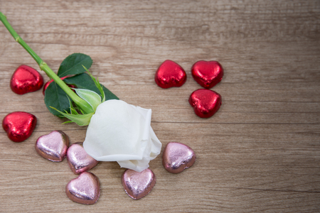 A white rose with heart shape chocolate on the wooden floor 스톡 콘텐츠