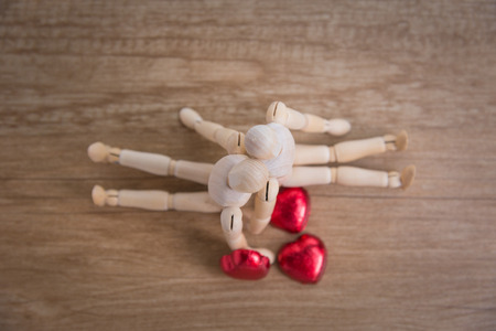 compose: A wooden doll man with heart-shaped chocolate in valentine day compose with love Stock Photo