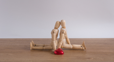 cuteness: A wooden doll man with heart-shaped chocolate in valentine day compose with love Stock Photo