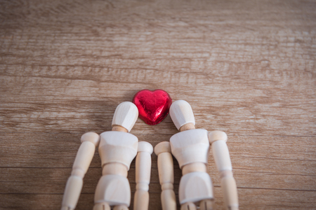 cuteness: A couple of wooden doll man with heart-shaped chocolate are in love with each other