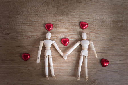 either: A couple of wooden doll man on valentine days showing love to each other and focus either on heart-shaped chocolate and the couple Stock Photo