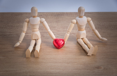 A couple of wooden doll man on valentine days showing love to each other and focus either on heart-shaped chocolate and the couple Stock Photo